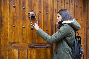Chica joven llamando a la puerta