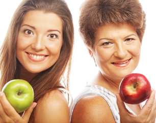Middle age woman with her daughter holding apples