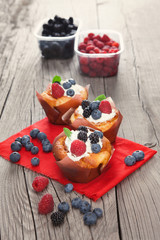 Cupcakes with berries on wooden table