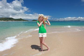 沖縄のビーチでビールを楽しむ笑顔の女性