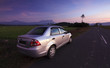 Car parked on roadside in a rural area at sunset