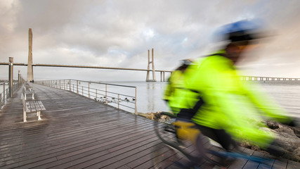 Blurred bicycle riders on promenade in front of of Vasco da Gama