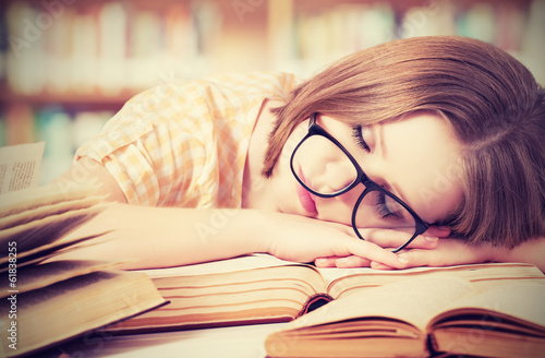 Leinwanddruck Bild tired student girl with glasses sleeping on books in library