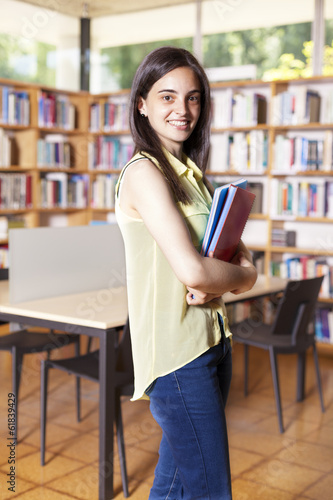 Happy female student holding books at the library