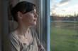 Junge, traurige Frau am Fenster