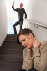 Junge Frau sitzt auf Treppe, häusliche Gewalt, Bedrohung
