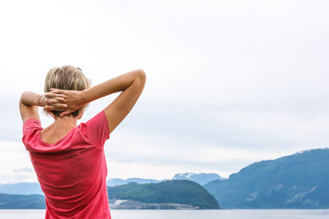 Back view of a woman enjoying a view at fjord