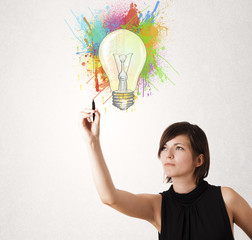 Young lady drawing a colorful light bulb with colorful splashes