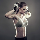 Athletic young woman doing a fitness workout over grey