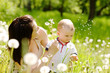 Young mother and her cute son blowing dandelion flowers together