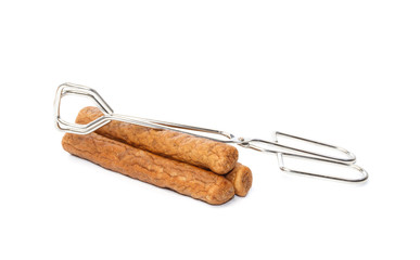 Three frikandellen with frying tongs