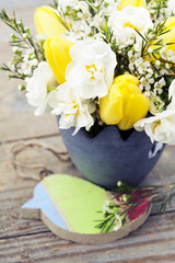 Bouquet of tulips and daffodils in vase on wooden background