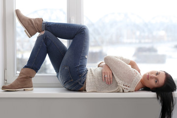 Attractive girl on the window sill