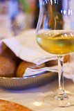 Glass of white wine and fresh bread in restaurant.