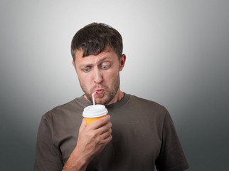 Funny man drinking from a disposable paper cup with a straw
