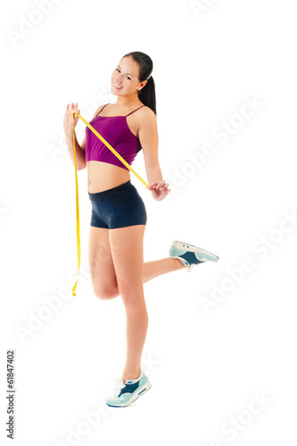 young woman holding a measure tape around her waist
