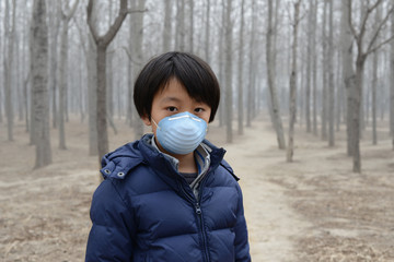 Asian boy wearing mouth mask standing in front of dry forest
