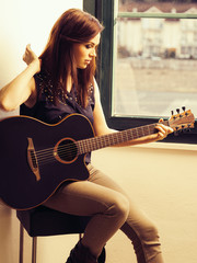 Beautiful brunette playing acoustic guitar