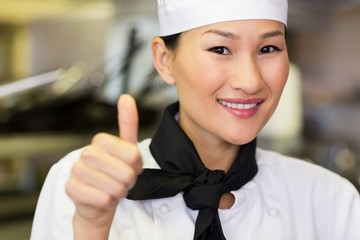 Portrait of smiling female cook gesturing thumbs up