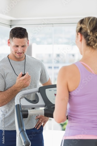 Trainer watching woman exercising at gym