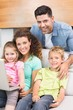 Happy family sitting on sofa using laptop