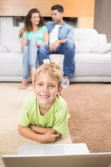Happy little boy using laptop on the rug with parents sitting so