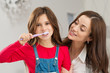 Girl With Her Mother Brushing Teeth