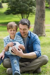 Father and son sitting with ball at park