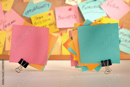 Paper notes fastened with paper clips, message board.