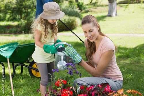 Mother with daughter watering plants