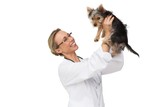 Vet holding up yorkshire terrier puppy and smiling