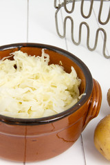 part of bowl filled with sauerkraut and masher on the background