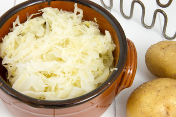 detail of bowl filled with sauerkraut, masher and potatoes