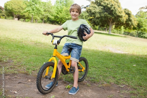 Smiling boy riding bicycle at park