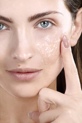 Beautiful woman applying scrub treatment on face