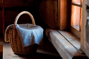 wicker basket covered with a rough cloth on the bench in the hut