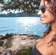 Sexy woman in white bikini near edge of infinity pool looking fa