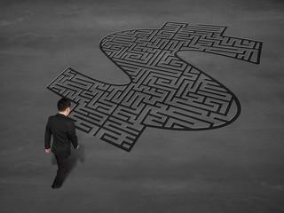 walking toward money shape maze on concrete ground