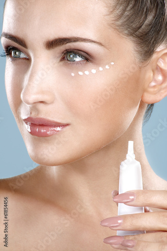Beautiful woman applying cream treatment on her perfect face