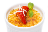 creme brulee garnished with strawberries on a white background