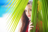 A beautiful young girl looking through palm leaves, tropical vac