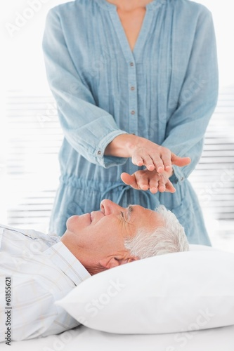 Therapist performing Reiki over forehead of man