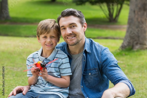 Boy with toy aeroplane sitting on father's lap at park