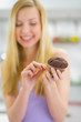 Closeup on young woman eating chocolate muffin