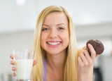 Portrait of happy young woman with milk and chocolate muffin