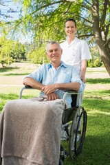 Woman with her father sitting in wheel chair at park