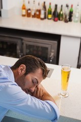 Drunk businessman sleeping beside glass of beer