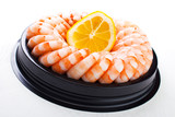 Shrimp ring on plastic platter with slice of lemon