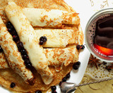 Pancakes, rolled into tubes and a glass of hot mulled wine