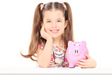 Little girl sitting at a table and holding piggybank